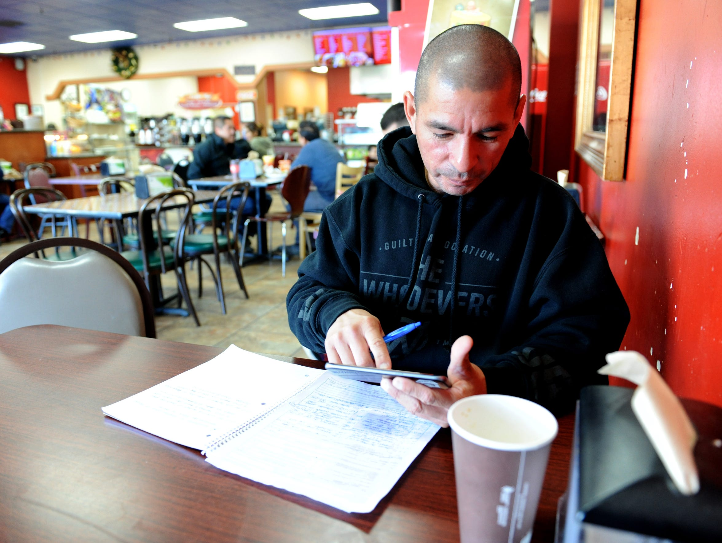 Placencia works on paperwork for his company and nonprofit at La Plaza Bakery on Davis Road on Salinas.