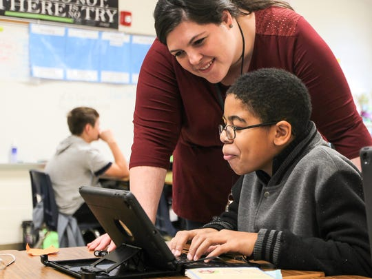 Fifth-grader Rykevieus Fleming shows teacher Darla Moore his work at Flat Rock Elementary School in Anderson, while doing a lesson on an iPad.