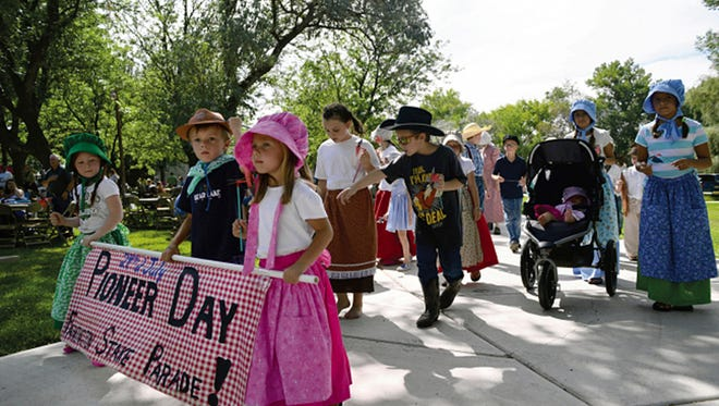 Participants in a Pioneer Days celebration march through Taylor Park in Farmington on July 26, 2014..