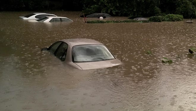 Cars were flooded Sunday in the backyards of homes along Vine Street near East Mitchell Avenue. The weather services said 3 to 5 inches of rain fell between 6 p.m. and 8:30 p.m. in Cincinnati.