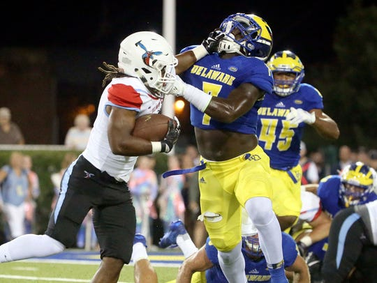 Delaware State running back Brycen Alleyne is stopped for a loss by Delaware's Ray Jones on third and goal from the one-yard line in the second quarter at Delaware Stadium last season.