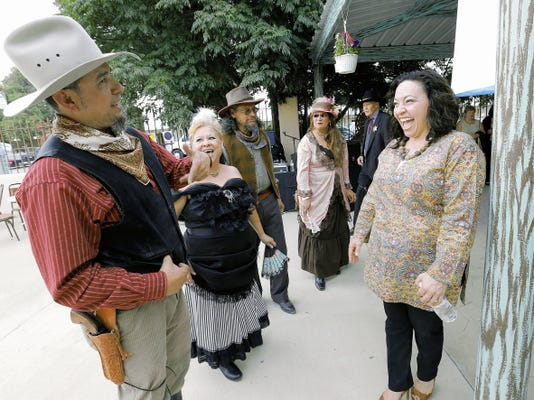 San Elizario Mayor Maya Sanchez, right, has a laugh with Old West reenactment group Los Pistoleros de San Elizario as they celebrate the city's first City Hall at 12710 Church.