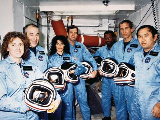 """STS-51L crew members pose during a break in countdown training in the White Room at Launch Pad 39B in November of 1985. From the left are Christa McAuliffe, Gregory Jarvis, Judith Resnik, Francis """"Dick"""" Scobee, Ronald McNair, Mike Smith and Ellison Onizuka."""