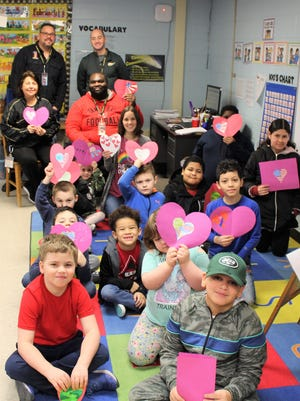 Students in the Buddy Program Class hold up their Valentines cards that they made for veterans.