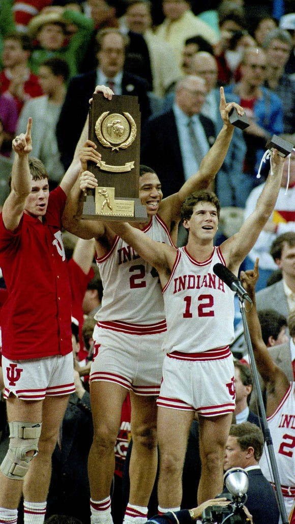 Indiana players Todd Meier, left, Daryl Thomas, center, and Steve Alford hold the trophy as they celebrate their winning the NCAA Championship over Syracuse in New Orleans Monday, March 30, 1987. The three are the team's  seniors and co-captions. (AP Photo/Bill Haber)