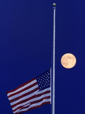 FILE- In this Aug. 31, 2012 file photo, an American flag flies at half-staff in honor of the passing of the first person to walk on the moon, Neil Armstrong, in front of the rising moon at a baseball park in Richmond, Va. Nearly every day somewhere in the country, the Stars and Stripes fly low, ordered to half-staff in one of the most significant official gestures of mourning and respect. (Dean Hoffmeyer/Richmond Times-Dispatch via AP, File)