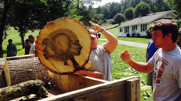 Enka football players help remove the tree in Monday's fatal car wreck involving sophomore lineman Christopher Taylor.