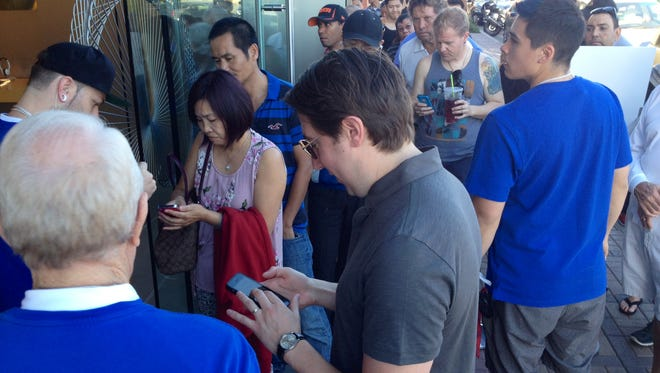 Hundreds of people lined up outside the Apple store on El Paseo in Palm Desert to buy the iPhone 6. The latest model was released Friday.