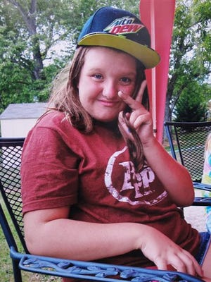 In this 2015 photo provided by Tammy Weeks, her daughter, Nicole Lovell, flashes a peace sign in Blacksburg, Va. The 13-year-old girl was found dead just across the state line in Surry County, N.C., and two Virginia Tech students are charged in the case. (Tammy Weeks via AP)