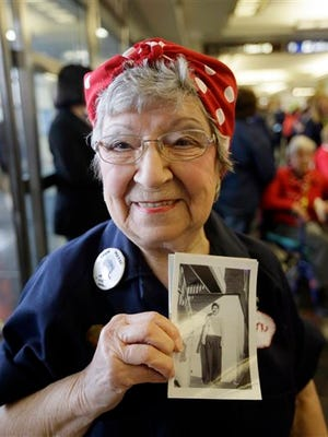 Former Rosie, T. Ogden of Aurora, Ill. shows a photo of herself after greeting fellow Rosies from Michigan on their arrival at the Ronald Reagan Washington National Airport, Tuesday, March 22, 2016 in Washington.