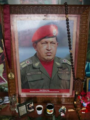 A photo of Venezuela's late president Hugo Chavez is seen inside of small chapel with two cups of coffee as a offering at the 4F military museum to commemorate what would have been the leader's 62th birthday, in the 23 de Enero neighborhood of Caracas, Venezuela, Thursday, July 28, 2016. With Chavez's hand picked successor Nicolas Maduro as President the socialist government of Venezuela is digging in its heels to stop a presidential recall vote as it fights to hold onto power amid an economic collapse. (AP Photo/Ariana Cubillos)