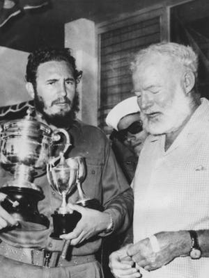 FILE - In this May 15, 1960 file photo, American novelist Ernest Hemingway, right, stands with Cuba's leader Fidel Castro who holds a trophy after winning the individual championship in the annual Hemingway Fishing Tournament in Havana, Cuba.  For many artists, Fidel Castro was a contradiction they never quite resolved, a man equally hard to embrace or to ignore. He was the bold revolutionary who defied the U.S. government and inspired the left worldwide and the long-winded despot who reminded them of the right-wing leaders they had traditionally opposed.