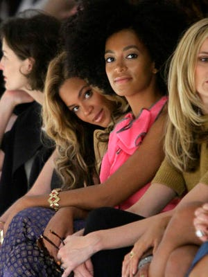 FILE - In this Sept. 13, 2011, file photo, Beyonce Knowles, center left, sits with her sister Solange Knowles during the presentation of Vera Wang's Spring 2012 collection in New York. Beyonce interviewed Solange for Interview magazine in a conversation published online on Jan. 10, 2017.