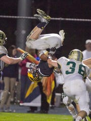 Hartland's Tommy Lappin dives and flips over a Howell tackle in the second quarter of the game Friday, Oct. 13, 2017.