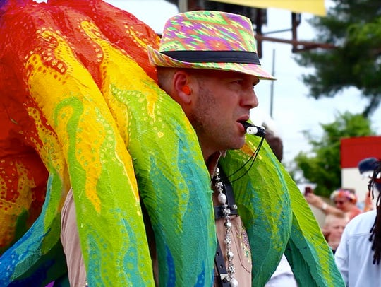 A marcher carries a vibrant, rainbow octopus while drumming in the Cattywampus Puppet Parade at Open Streets on Magnolia Avenue on Sunday, May 21.