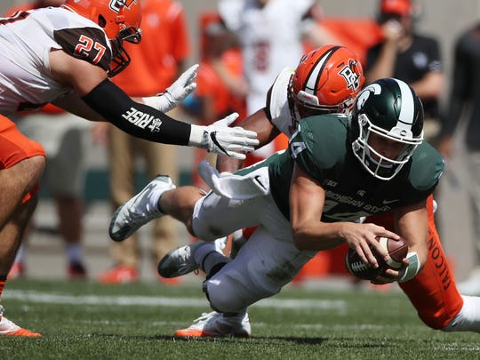 Brian Lewerke of the Michigan State Spartans dives for a first down past Nate Locke #27 of the Bowling Green Falcons during the second half at Spartan Stadium on September 2, 2017 in East Lansing, Michigan. Michigan State won the game 35-10.