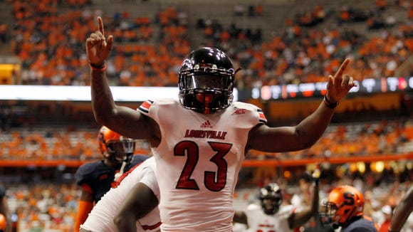 Louisville?s Brandon Radcliff celebrates scoring a touchdown in the first quarter of an NCAA college football game against Syracuse in Syracuse, N.Y., Friday, Oct. 3, 2014. (AP Photo/Nick Lisi)