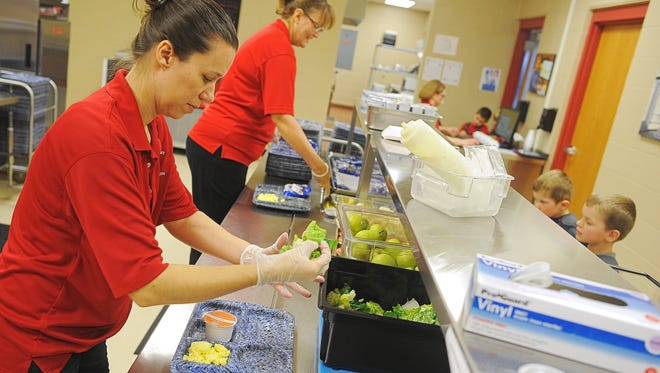 Angel Dunham, kitchen manager at Fred Assam Elementary School, dishes up a tray of food for a student during lunch at Brandon Valley School District's Fred Assam Elementary School Thursday, Jan. 21, 2016, in Sioux Falls. Thursday's lunch menu at Fred Assam Elementary consisted of scrambled eggs, pancakes, orange juice, salad, cauliflower and pears.