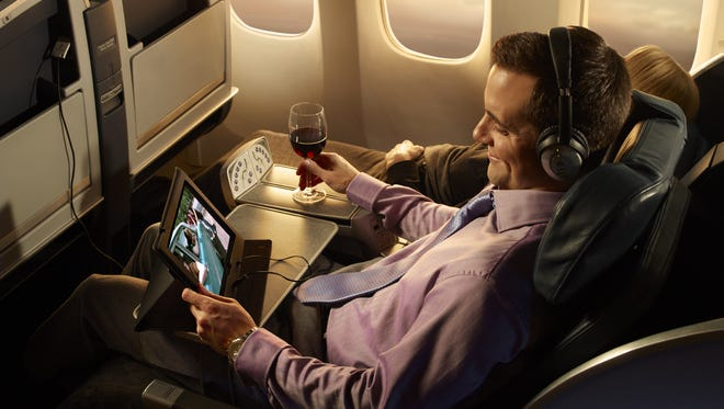 A passenger enjoys entertainment on his tablet during a flight.