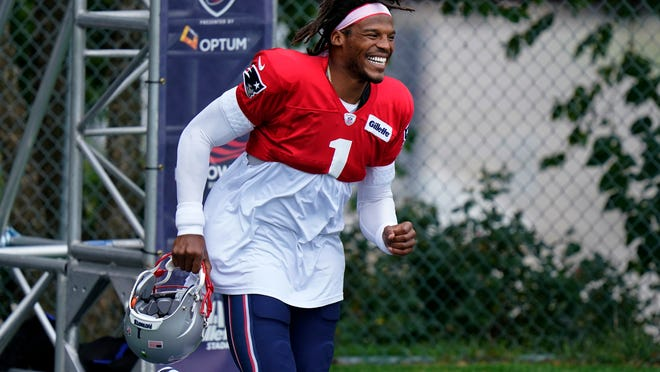 New England Patriots quarterback Cam Newton smiles as he steps on the field at the start of an NFL football training camp practice, Thursday, Aug. 27, 2020, in Foxborough, Mass.