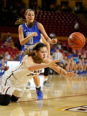 Arizona State's Sophie Brunner passes the ball while falling and being guarded by Middle Tennessee's Mackenzie Sells during the second half of a game on Friday, Nov. 14, 2014, in Tempe.