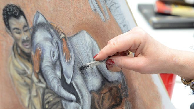 The hand of pastel artist Valerie Bayer works on a drawing inside Milford's SHAC.