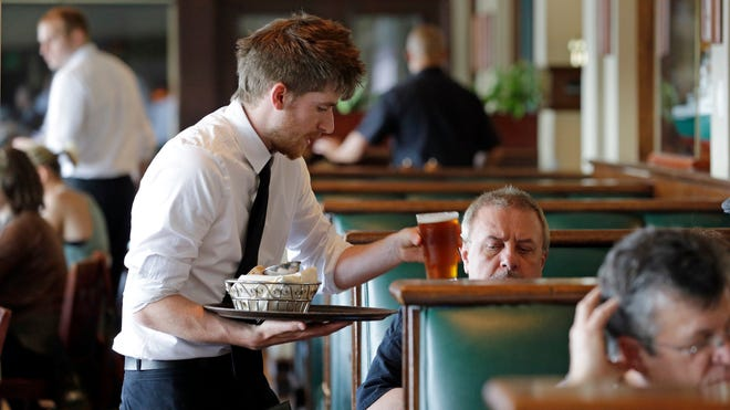 Waiter Spencer Meline serves a customer at Ivar's Acres of Clams restaurant on the Seattle waterfront on May 14, 2014.