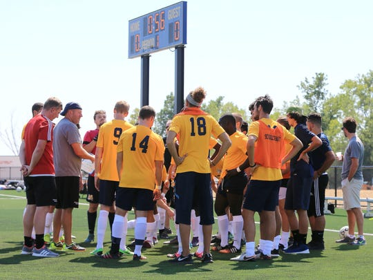 Schoolcraft College men's soccer players listen to