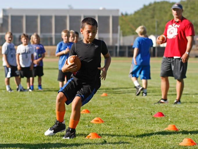 Tavian Smith, 9, a running back with the Juniors Peewee Olys, a Pop Warner team consisting of fourth, fifth and sixth graders, takes part in a drill during practice at Sprague High on Thursday, Aug. 7, 2014.  Participation is up significantly in the Salem-Keizer Pop Warner football league this year