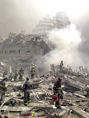 New York City firefighters and emergency personnel wander about Ground Zero on Sept. 11, 2001.