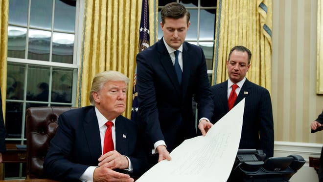 Ex- White House staff secretary Rob Porter, center, hands President Trump a confirmation order in the Oval Office on Jan. 20, 2017, as ex-White House chief of staff Reince Priebus watches.