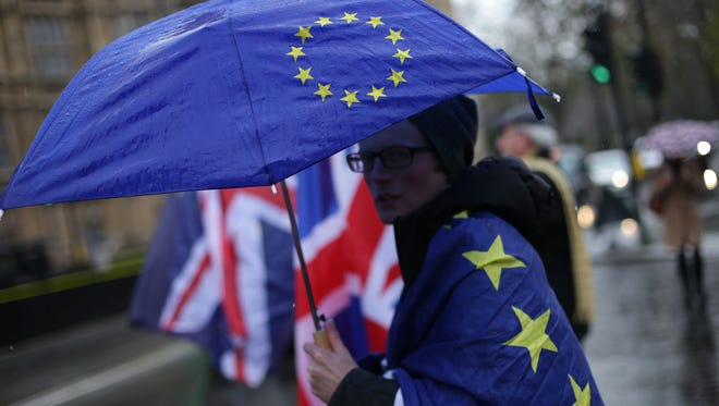 A pro-European Union, anti-Brexit demonstrator holds an umbrella with the EU flag outside the Houses of Parliament, in central London on Dec. 13, 2017.
