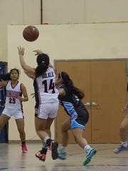 Okkodo junior Shania Bulala, 14, dishes an assist to Danica Cabrera in the Bulldogs 43-31 IIAAG Girls' Basketball League win against the St. Paul Warriors at Okkodo on Tuesday, Dec. 1.