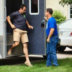 Jared Fogle, left, who rose to fame as the Subway pitchman, steps from a police evidence truck parked in the driveway of his Zionsville, Ind., home on July 7, 2015.