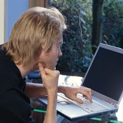 Man using laptop computer in his home office.