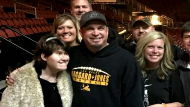 """Garth Brooks shares a moment with fan McKenna """"Mickey"""" Phernetton during his tour stop in Louisville, Kentucky."""