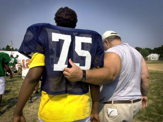 Brad Livingston, right, puts his arm around former