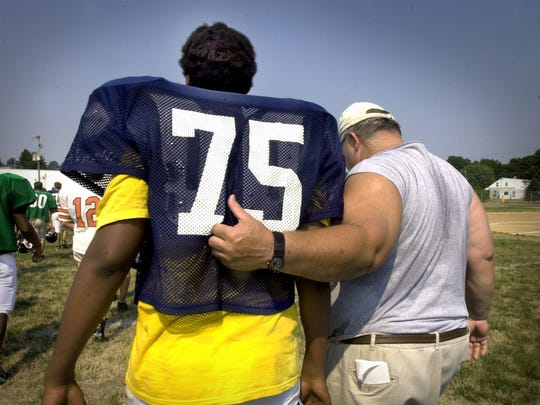 Central York football coach Brad Livingston is dwarfed by Will Beatty during a 2002 practice. Beatty went on to graduate from William Penn and reach the NFL, where he has played on the New York Giants offensive line since 2009.
