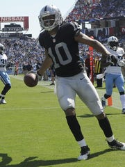 Raiders wide receiver Seth Roberts prepares to throw a ball in celebration after scoring a touchdown against the Tennessee Titans on Sept. 25, 2016 in Nashville.
