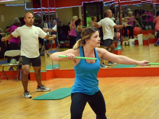"Brittani Stout (front, right), a Pound instructor at the Courtyard Health & Racquet Club in Alexandria, leads one of three Pound classes that the Courtyard offers. ""It's a really good workout for your core and your whole body,"" said Diego Quesada (back, f"