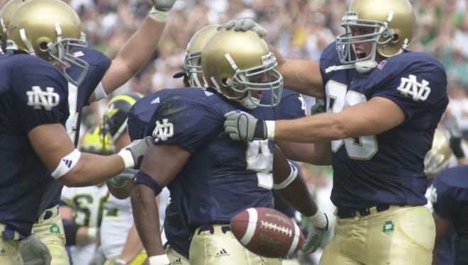 Notre Dame 's Ryan Grant second form right is mobbed by his teammates after he scored the first offensive touchdown of the season in the first quarter of a win over Michigan.