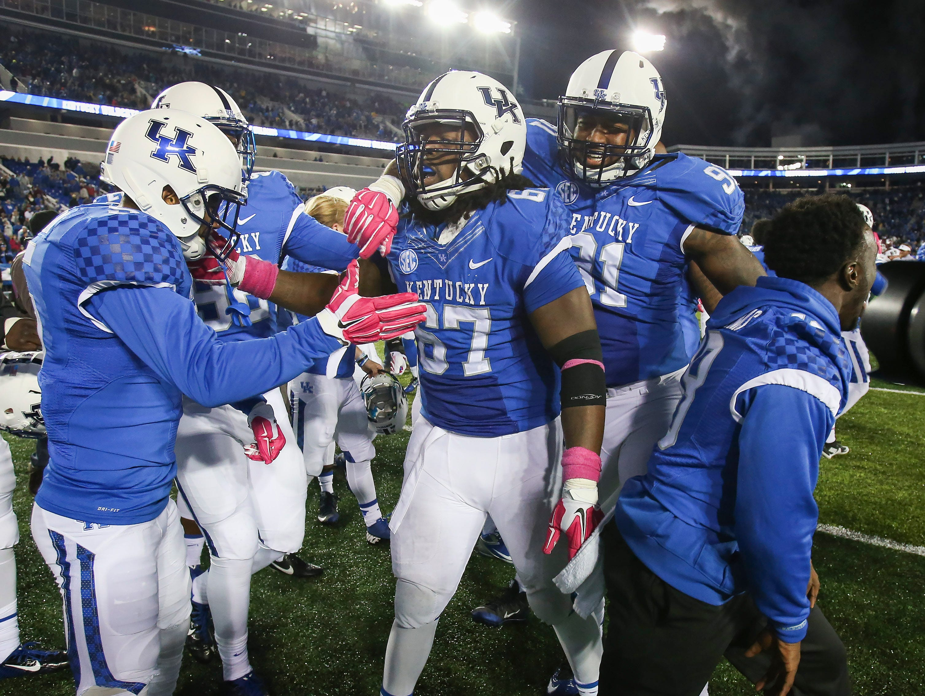 Kentucky cornerback Kendall Randolph, left, defensive tackle Cory Johnson, center, and defensive end Farrington Huguenin celebrate after defeating Eastern Kentucky in overtime during an NCAA college football game Saturday, Oct. 3, 2015, in Lexington, Ky. (AP Photo/David Stephenson) 5, 67, 91