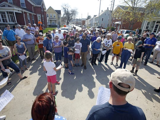Members of the community gather Sunday, April 17, at the site of last week's cross burnings in Dubuque.