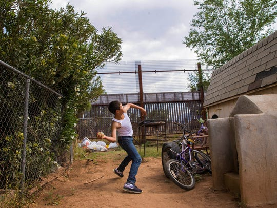 Manny Amaya, 13, attempts to throw a water balloon