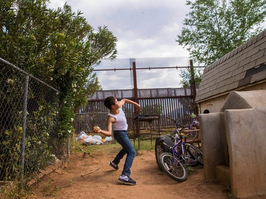 Manny Amaya, 13, attempts to throw a water balloon over the double border fence in the backyard of his home in Naco, Arizona.