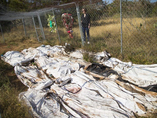 Kate Spradley stands near body bags that contain remains