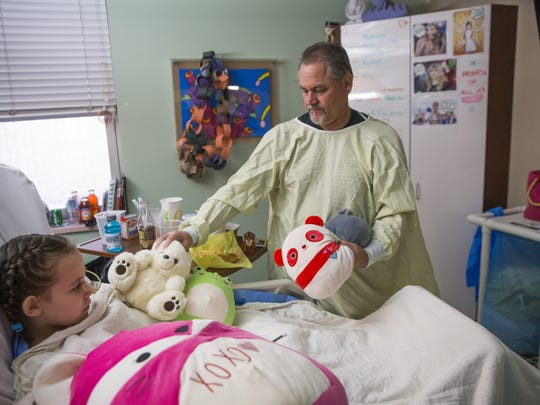 Eight-year-old Isabella McCune with her father, J.D., at the Arizona Burn Center at Maricopa Medical Center in Phoenix.