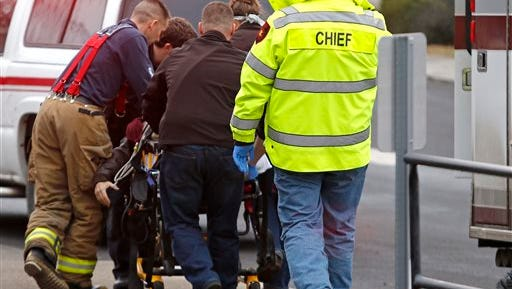 Emergency medical technicians rush one of two shooting victims to an ambulance after they were shot in an office in Moscow, Idaho, on Saturday.