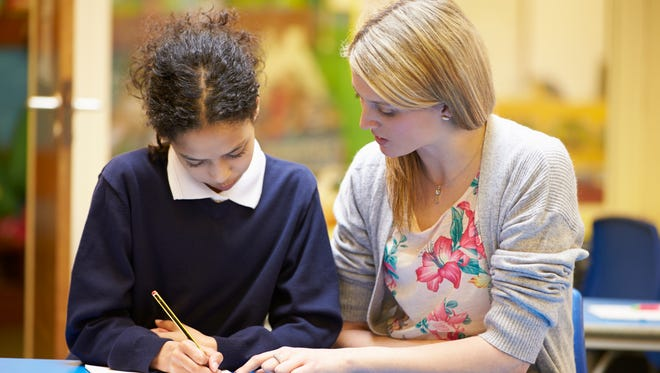 Teacher With Female Pupil Reading At Desk In Classroom Writing In Notebook.