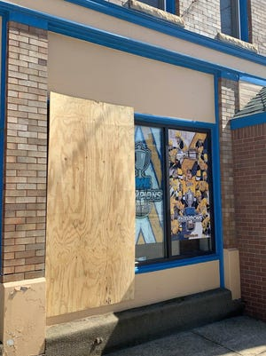 A window at the Erie Otters' office downtown has been covered by a board after the window was broken during a protest Saturday, May 30, 2020.